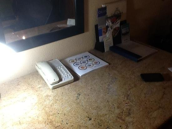 Wyndham Garden Oklahoma City Airport: the desk with a cordless phone in front of a mirror