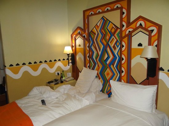 AVANI Victoria Falls Resort : The cozy bed and wall paintings