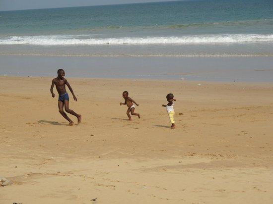 Busua Inn: Enfants sur la plage devant l'hotel
