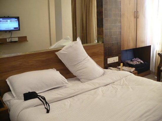 United-21 Resort Mahabaleshwar: the bed room with hardy any space on either side of the bed