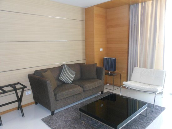 Anantara Sathorn Bangkok Hotel: Sofa facing the TV. Balcony behind the curtains