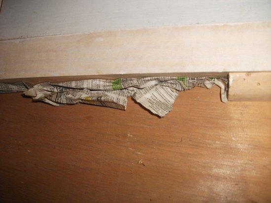 Cabañas Pinares Del Mar: Rendija de la puerta principal tapada con papel de diario