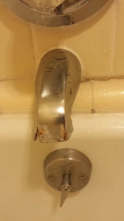 Americas Best Value Inn & Suites: Rusted bathtub faucet (Dirty tub & filthy shower curtain not pictured)