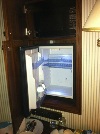 Regency House Hotel: Fridge above a small table with plates & cutlery