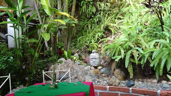 Restaurant Gaby's: Back wall with greenery and fountain stream.