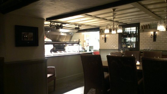 The Grill & Smokehouse Restaurant: View of the kitchen grill (home of the steaks) from table.