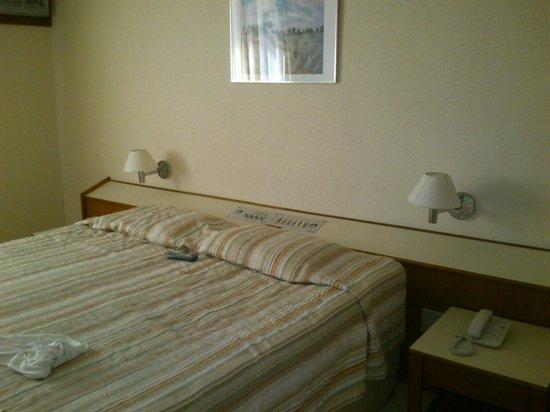 Atlântico Copacabana Hotel : Imagen de la cama con los controles unificados detras...