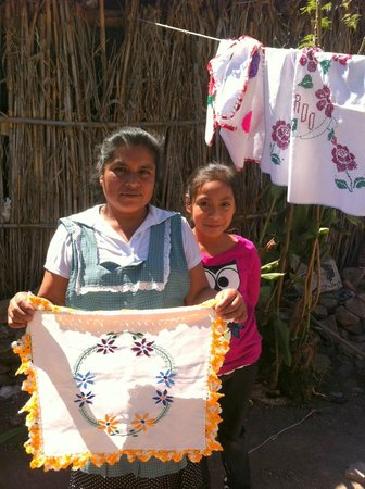 Fundacion En Via : En Via daughter and her client show mom's embroidery.