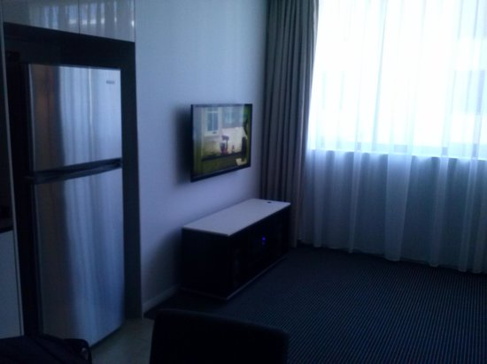 Meriton Suites North Ryde: tv and fridge