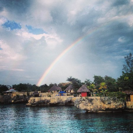 An afternoon rainbow arches above the Rockhouse Hotel's cliffside property