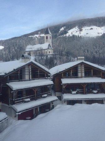 Post Alpina - Family Mountain Chalets: Anlage mit der Kirche von Vierschach im Hintergrund