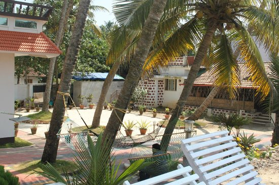 Palm Beach Resort: garden, hammocks and on the right the restaurant