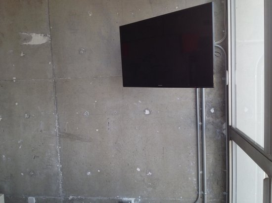 The Line: Overhead TV against exposed concrete wall.