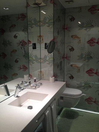 Hotel Santo Domingo Madrid : Baño con suelo de cristal y arena debajo, paredes decristal y peces pintados en papel