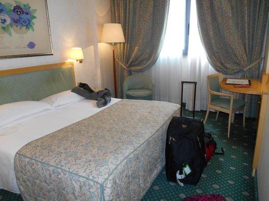 ADI Hotel Poliziano Fiera: bedroom with desk and TV on the right
