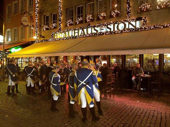 """Brauhaus Sion: Вход в Сион с рождественскими украшениями. Перед входом- карнавальная """"гражданская гвардия""""."""
