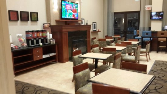 Hampton Inn & Suites Newark-Harrison-Riverwalk : Acogedora área del desayuno, con chimenea y televisión