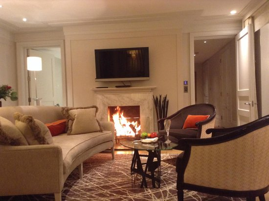 Coworth Park - Dorchester Collection: Cottage lounge with lit fire