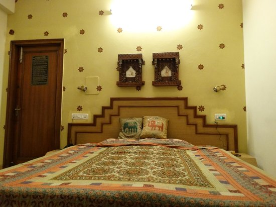 Hotel Pearl Palace : Double bed with decorative pieces hung up