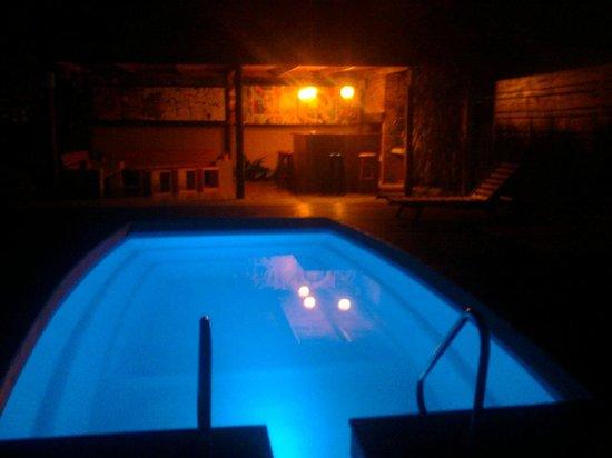 Posada El Capullo : Piscina en la noche, iluminada con distintos colores
