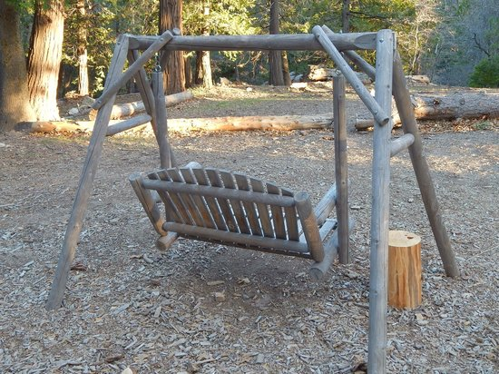 Arrowhead Pine Rose Cabins : outside wooden swing at backdoor