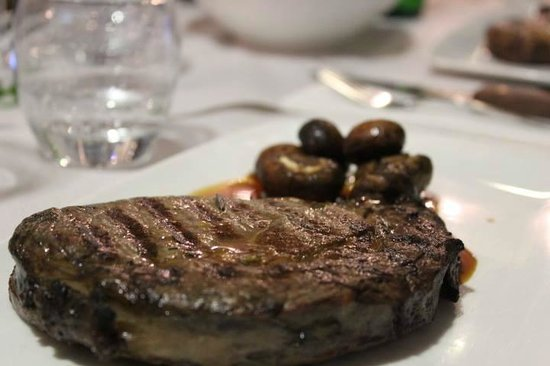 Shows a juicy cut of steak on a plate