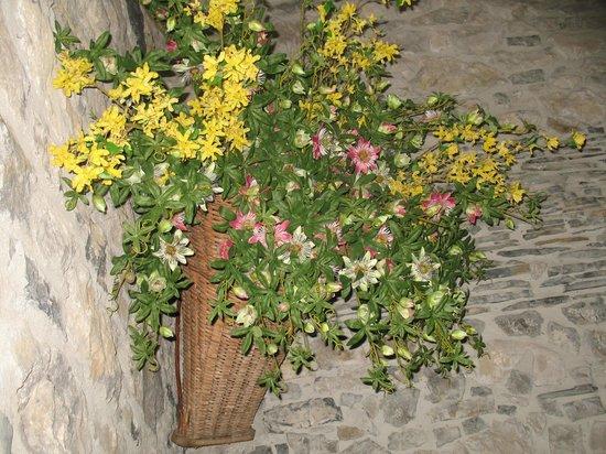 Agriturismo La Peta: Una gerla piena di fiori all'interno della sala da pranzo
