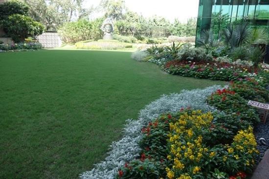 The Leela Palace New Delhi: hotel garden adjoining restaurant