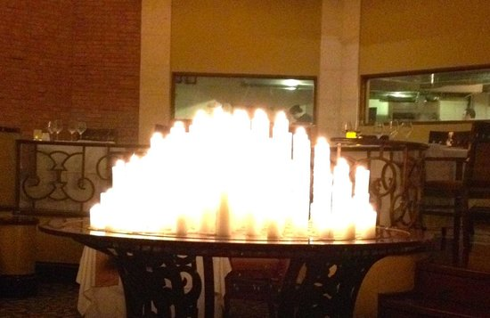 Gustino: beautiful table covered with pillar candles in the center of the restaurant