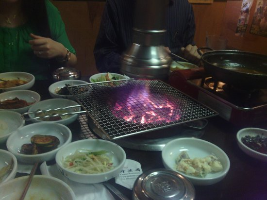 Gabose Korean & Japanese Rstrt: Charcoal grill in center of table, side dishes surrounding it.