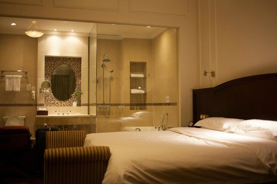 Astor House Hotel: bed with clear glass wall separating the bathroom