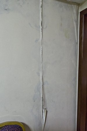 Tianzhi Hotel Harbin: Wallpaper peeling off the wall in our first room