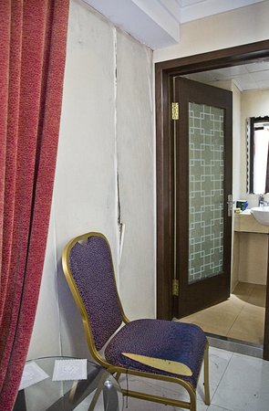 Tianzhi Hotel Harbin: Peeling wallpaper and threadbare chair in our first room