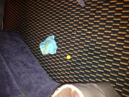 Travelodge New Orleans West Harvey Hotel: Dirty floor/ child clothes & toy found by ottoman