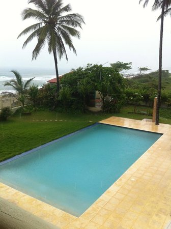 Barefoot Beach Pad: Pool area and beach from upper floor double room on cloudy day