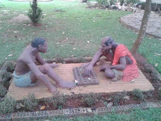 The sculpture of old men playing 'Omweso' at Banana Village