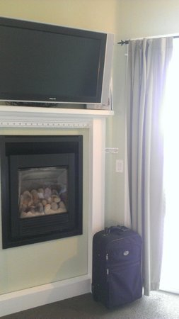 Beachfront Manor Hotel : Fireplace and flat screen TV next to patio door.
