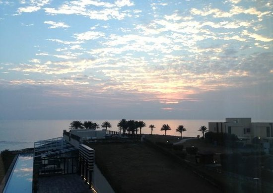 Hilton Kuwait Resort: Sunrise across the sea from our bedroom window dawn light reflected in the ornamental pool