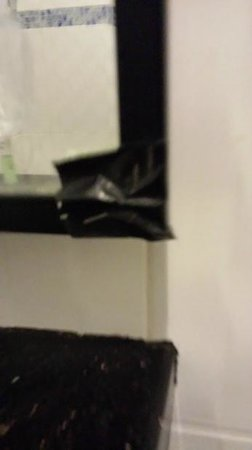 Hallmark Hotel: Bathroom mirror damaged and held in place with black electrical tape