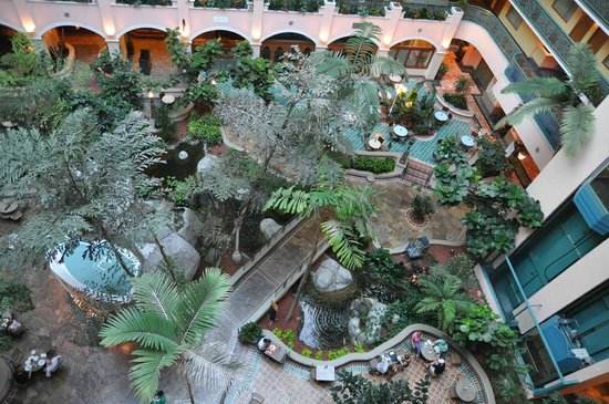 Embassy Suites Miami International Airport: Glass-roofed courtyard with lots of vegetation and water. The restaurant is over there.