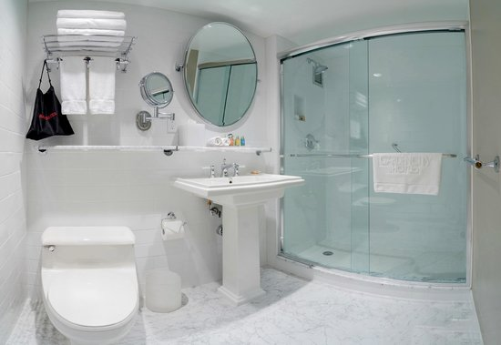 Garden City Hotel: Deluxe King Guest Bathroom with Glass Shower Doors and Carrera Marble Accents