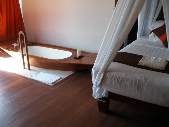 Pristine Lotus Spa Resort : Bathtub next to bed in room