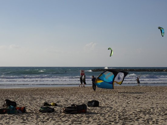 Herods Tel Aviv : Beach full of activity, surfers and parasailers.