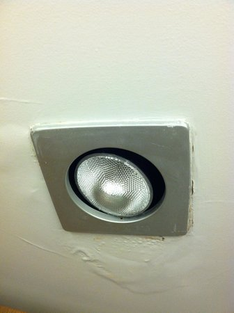 Embassy Suites by Hilton St. Paul - Downtown : light hanging awkwardly in the socket with uneven spackling all around it.