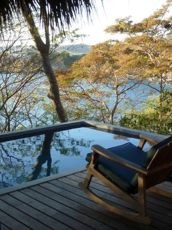 Aqua Wellness Resort: view of plunge pool overlooking tree canopies & ocean