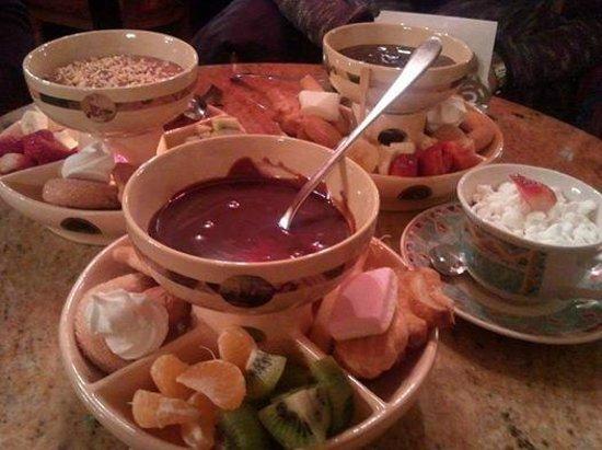 Fonduta di cioccolato al latte con biscotti e frutta foto di la