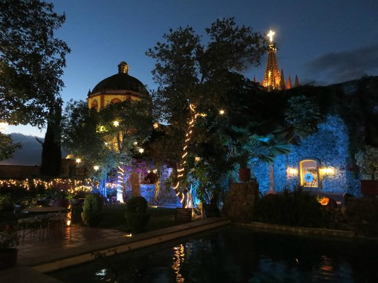 Coqueta Hotel Boutique: Pool & garden at night with Parroquia in the background