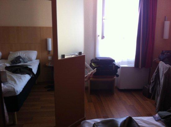 Ibis Montpellier Centre: une persone assise lit son journal dans les wc je prends la photo depuis le lit
