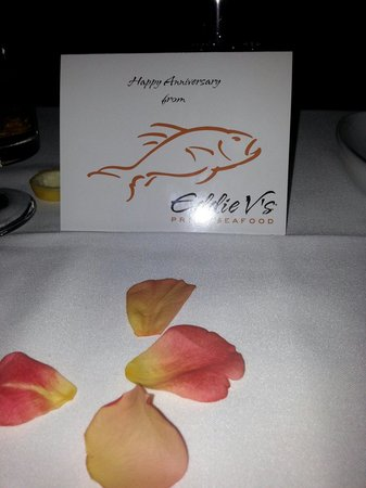 Eddie V's Prime Seafood: Happy anniversary card with rose petals on the table. A lovely touch from a lovely restaurant th