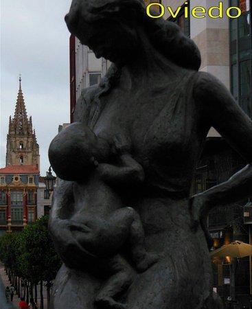 Esculturas Oviedo : Estatua que parece estar dedicada a la Maternidad, con la torre de la Catedral de fondo.